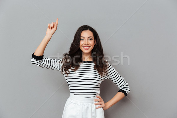 Portrait of a smiling woman pointing finger up Stock photo © deandrobot