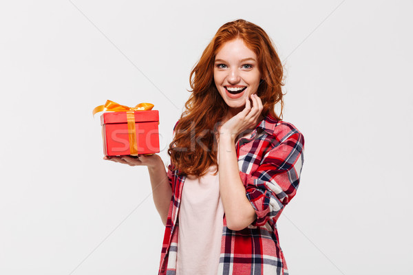 Image of Happy ginger woman in shirt holding gift box Stock photo © deandrobot