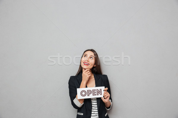 Pensive pleased business woman holding nameplate open while looking up Stock photo © deandrobot