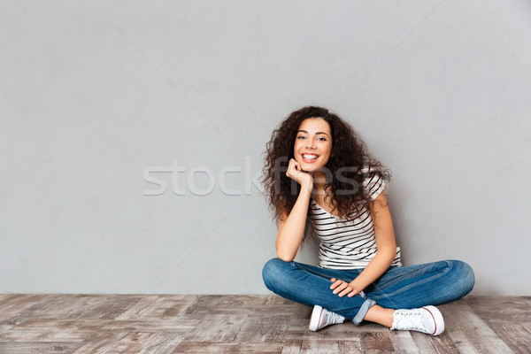 Lovely curly woman in casual clothes sitting in lotus pose on th Stock photo © deandrobot
