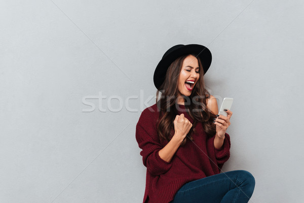 Brunette woman in sweater and hat using smartphone and rejoice Stock photo © deandrobot