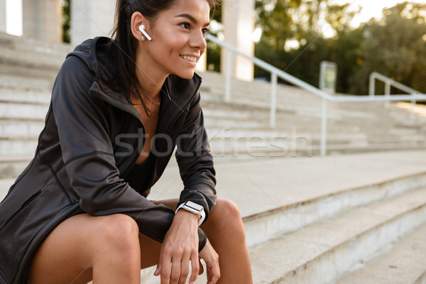Portrait of a smiling fitness woman in earphones Stock photo © deandrobot