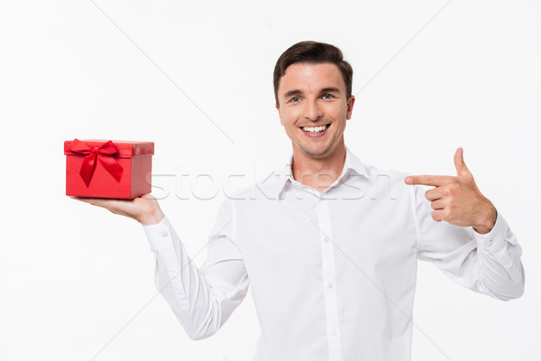 Portrait of a glad man in white shirt pointing finger Stock photo © deandrobot