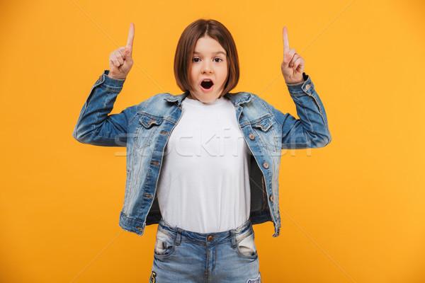 Retrato excitado pequeño colegiala senalando dos Foto stock © deandrobot