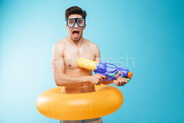 Portrait of a joyful young shirtless man in swim goggles Stock photo © deandrobot