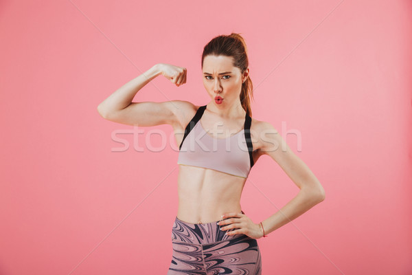 Pleased sportswoman posing with arm on hip while showing bicep Stock photo © deandrobot
