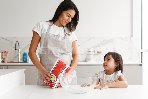 Happy brunette woman wearing apron cooking with her little daugh Stock photo © deandrobot