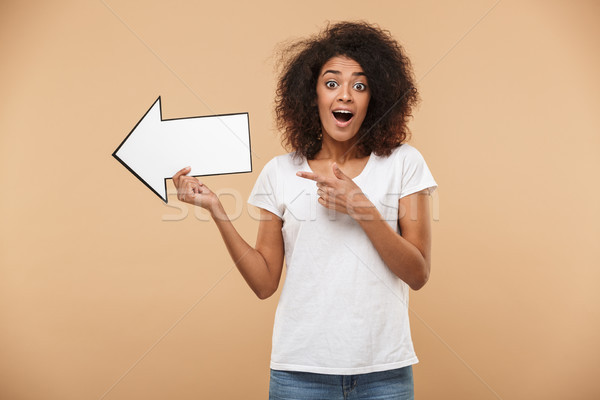 Portrait of an excited young african woman pointing away Stock photo © deandrobot