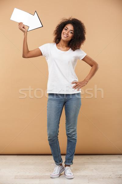 Full length portrait of an excited young african woman Stock photo © deandrobot