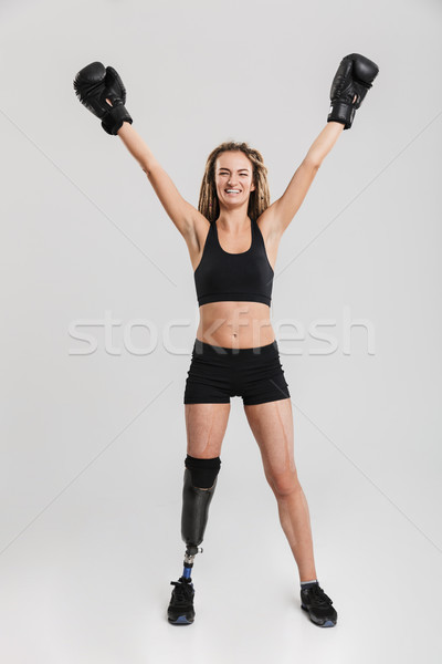 Healthy young disabled sportswoman boxer make winner gesture in gloves. Stock photo © deandrobot