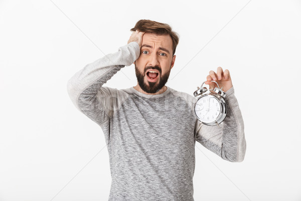 Screaming scared young man holding alarm clock. Stock photo © deandrobot