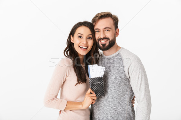 Cheerful young loving couple holding passport and tickets. Stock photo © deandrobot