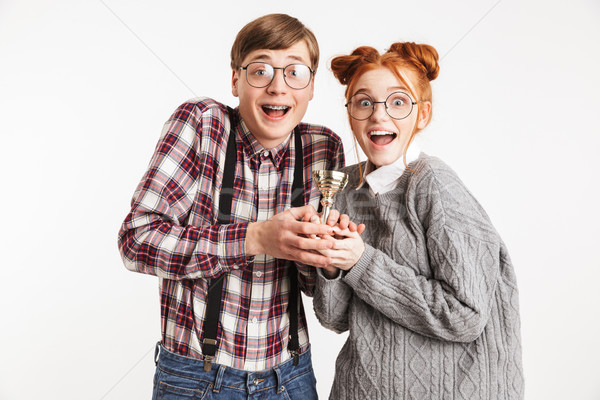 Happy couple of school nerds holding winners trophy Stock photo © deandrobot