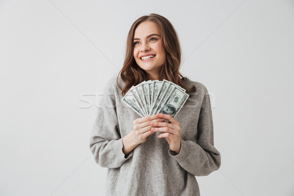 Smiling brunette woman in sweater holding money while looking away Stock photo © deandrobot