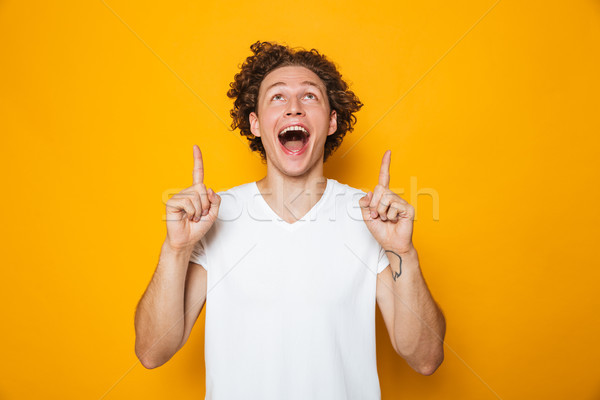 Excited cheerful man 20s with brown curly hair pointing finger u Stock photo © deandrobot