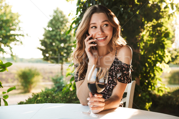 Woman sitting in cafe drinking wine talking by mobile phone. Stock photo © deandrobot