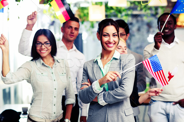 Happy group of businesspeople standing with flags in office Stock photo © deandrobot