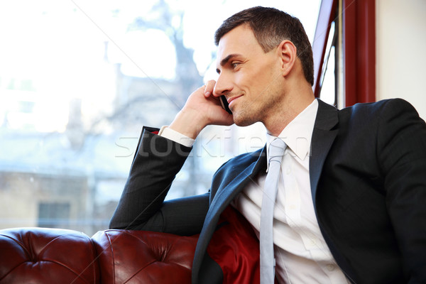 Smiling businessman talking on the phone and looking in window at office Stock photo © deandrobot