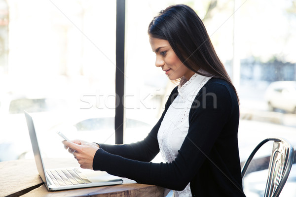 Stock photo: Happy businesswoman using smartphone in cafe