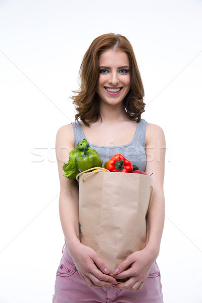 Smiling cute woman holding a shopping bag full of groceries Stock photo © deandrobot