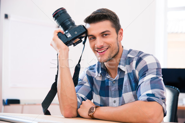 Man sitting at the table with camera  Stock photo © deandrobot