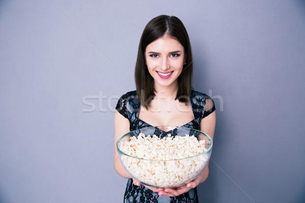 Boldog fiatal nő tart tál pattogatott kukorica szürke Stock fotó © deandrobot