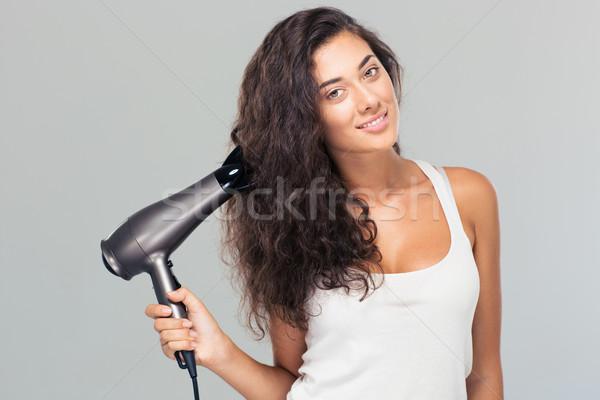 Feliz bela mulher secador de cabelo cinza olhando Foto stock © deandrobot