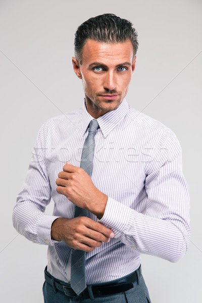 Businessman buttoning cuff sleeves Stock photo © deandrobot