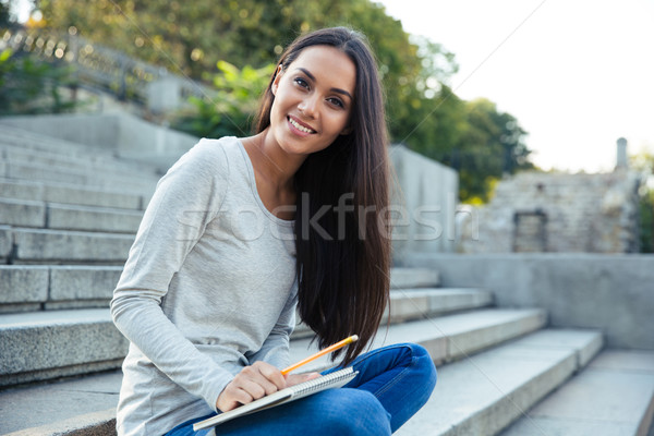 Ragazza seduta città scale matita notepad Foto d'archivio © deandrobot