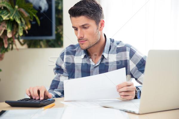 Man with calculator checking bills Stock photo © deandrobot