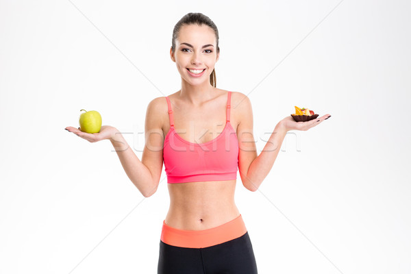 Cheerful young fitness girl holding healthy and unhealthy food Stock photo © deandrobot