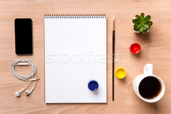 Notepad , paintbrush, paints, smartphone, earphones and cup of coffee  Stock photo © deandrobot
