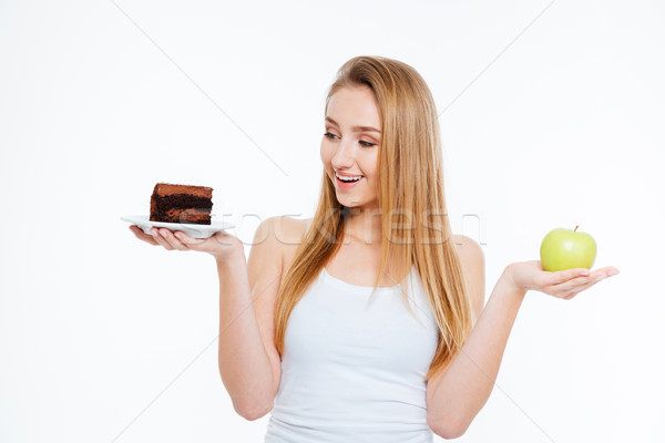 Happy woman holding chocolate cake and green apple Stock photo © deandrobot