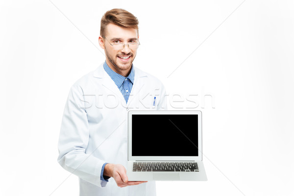 Male doctor showing blank laptop computer screen Stock photo © deandrobot