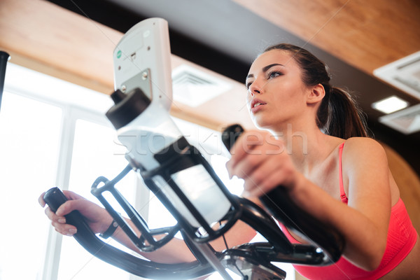 Focused sportswoman exercising on bicycle in gym Stock photo © deandrobot