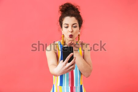 Lovely amusing young woman biting candy cane and winking  Stock photo © deandrobot