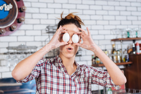 Woman covered eyes with eggs and having fun on kitchen Stock photo © deandrobot