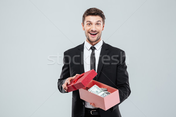 Happy excited young businessman holding gift box full of money Stock photo © deandrobot