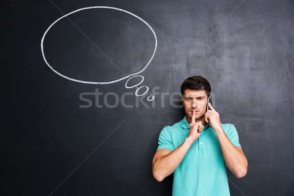 Man talking on cell phone and showing silence gesture Stock photo © deandrobot