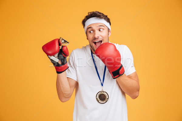 Man boxer in red gloves with trophy cup and medal Stock photo © deandrobot