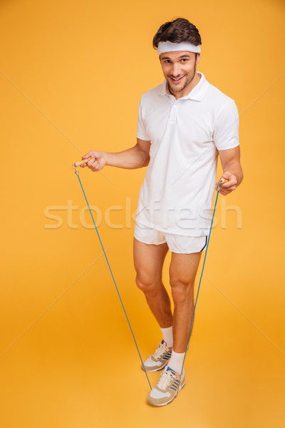 Full length portrait of a sportsman jumping with skipping rope Stock photo © deandrobot