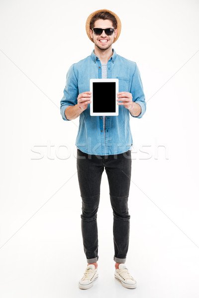 Smiling handsome young man standing and holding blank screen tablet Stock photo © deandrobot