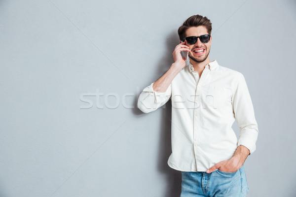Vrolijk jonge man zonnebril praten mobiele telefoon witte Stockfoto © deandrobot