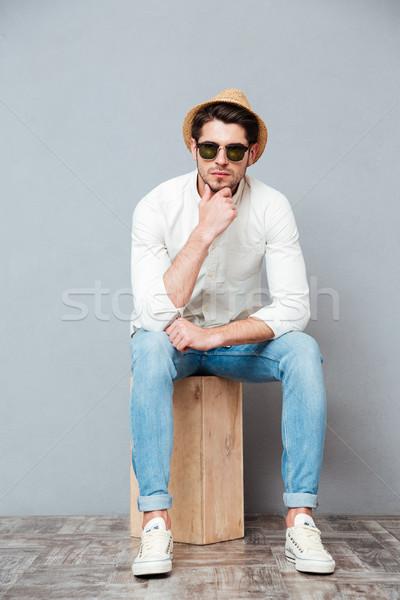Stock fotó: Töprengő · fiatalember · napszemüveg · ül · gondolkodik · kalap