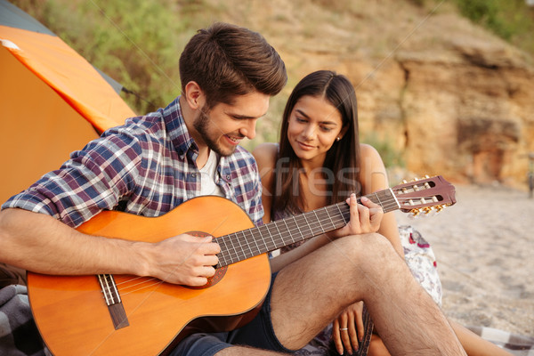 Stock photo: Man playing guitar for his girlfriend sitting at the tent
