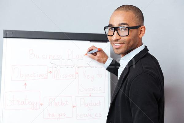 Man making presentation of business plan on flipchart Stock photo © deandrobot