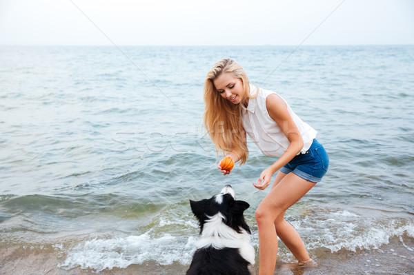 Feliz mulher jogar cão bola praia Foto stock © deandrobot