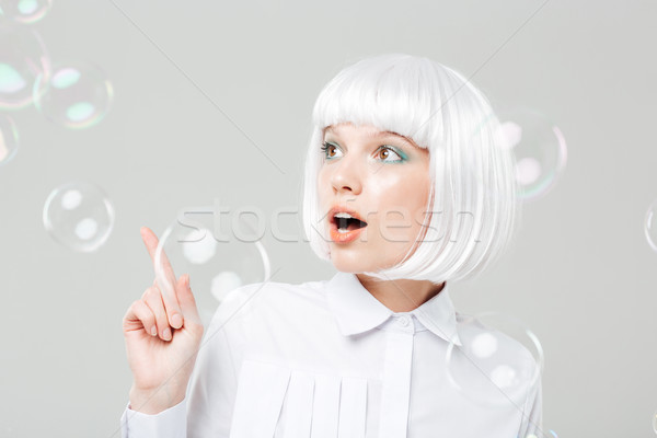 Lovely amazed woman looking at soap bubbles and pointing away Stock photo © deandrobot