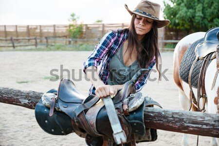 Beautiful young woman cowgirl sitting and riding horse in village Stock photo © deandrobot