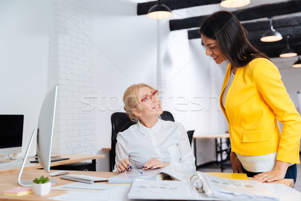 Businesswomen talking and smiling while reviewing a work plan Stock photo © deandrobot